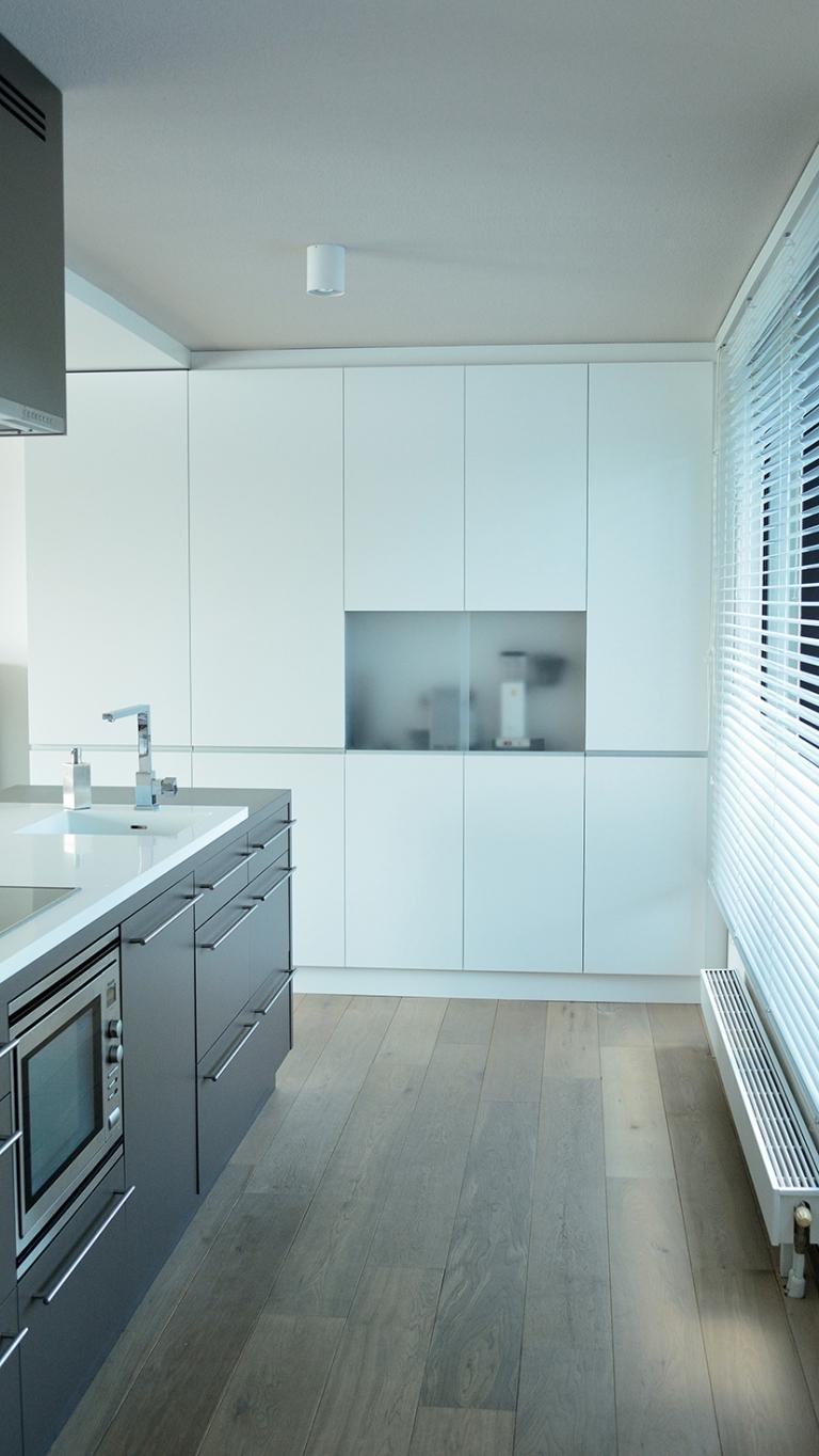 Hoge keukenkast gespoten in de twee componenten meubellak Achter matte plexiglas schuifdeuren bevinden zich verschillende keuken apparaten.